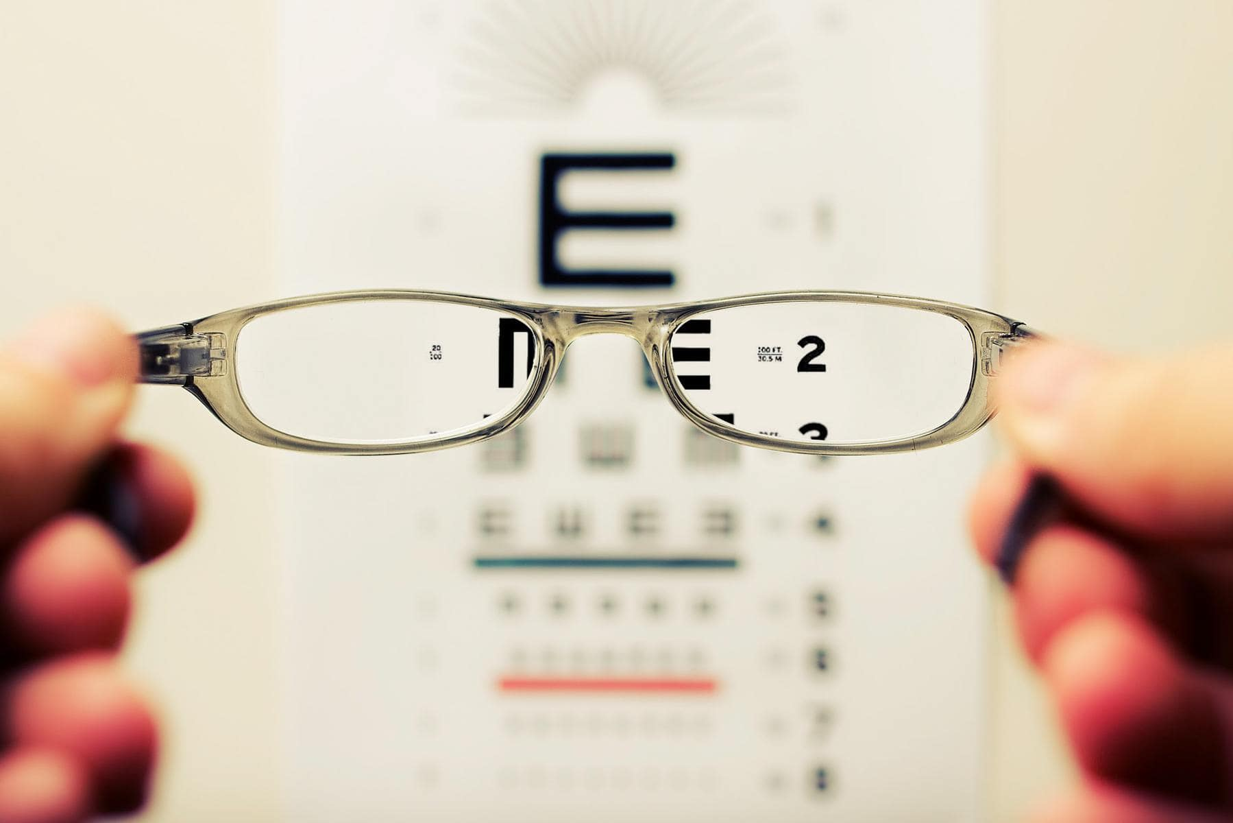 Image description: Eye chart seen through lenses of glasses; in the lenses the chart is in focus, otherwise it is blurry. Credit David Travis on Unsplash.