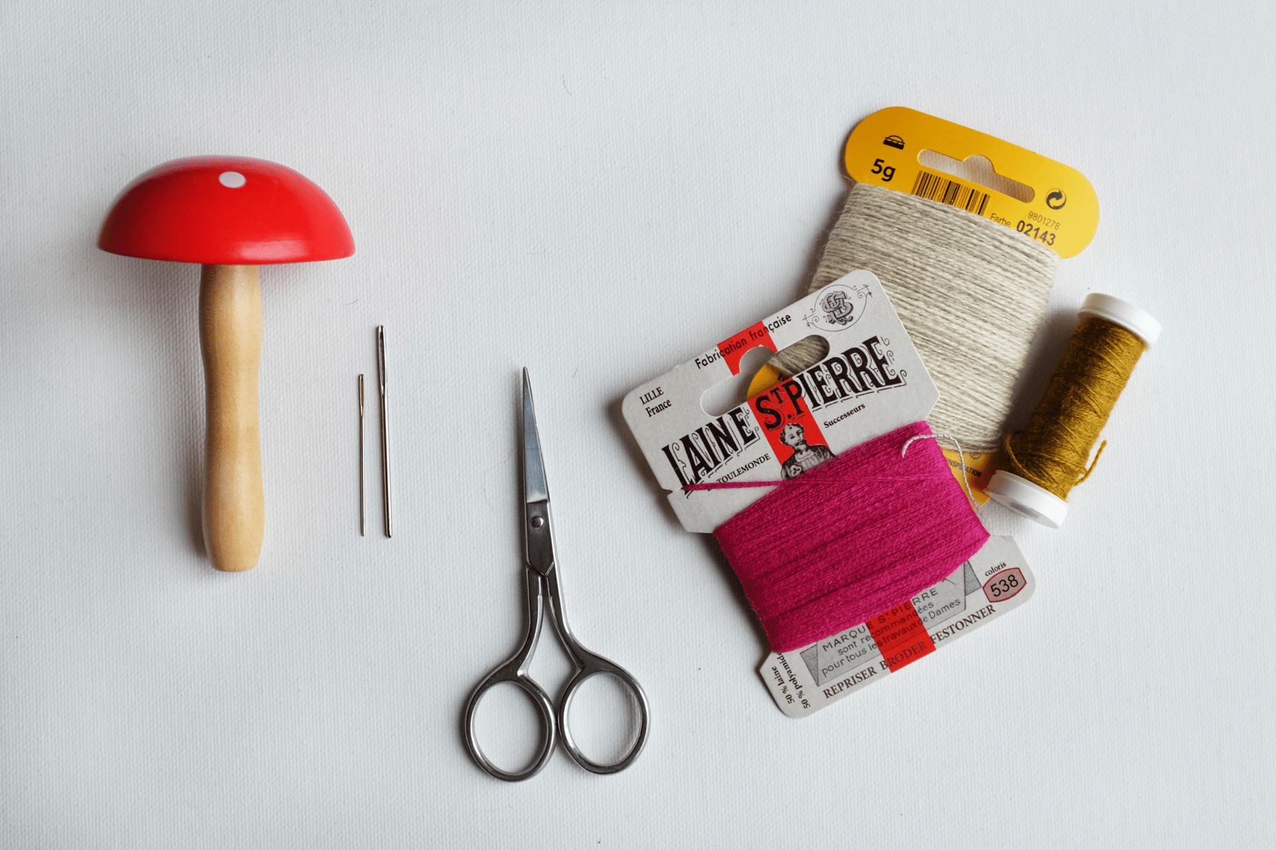 Image description: A flat-lay photo of mending supplies including a wooden darning mushroom, needles, embroidery scissors, and thread.
