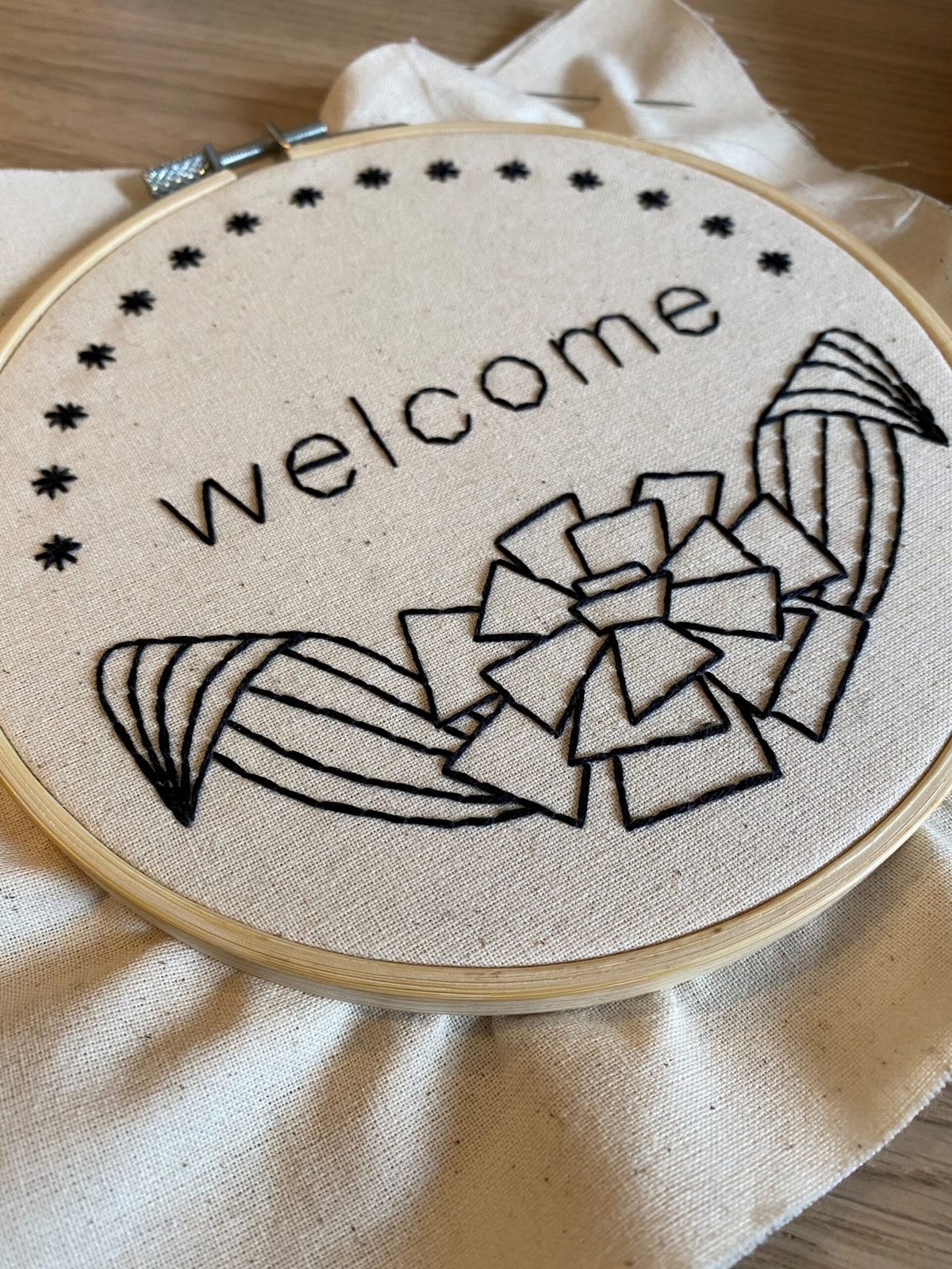 """Image description: Embroidery project in a hoop, photographed at an angle. The embroidery is in black thread and says """"welcome."""""""