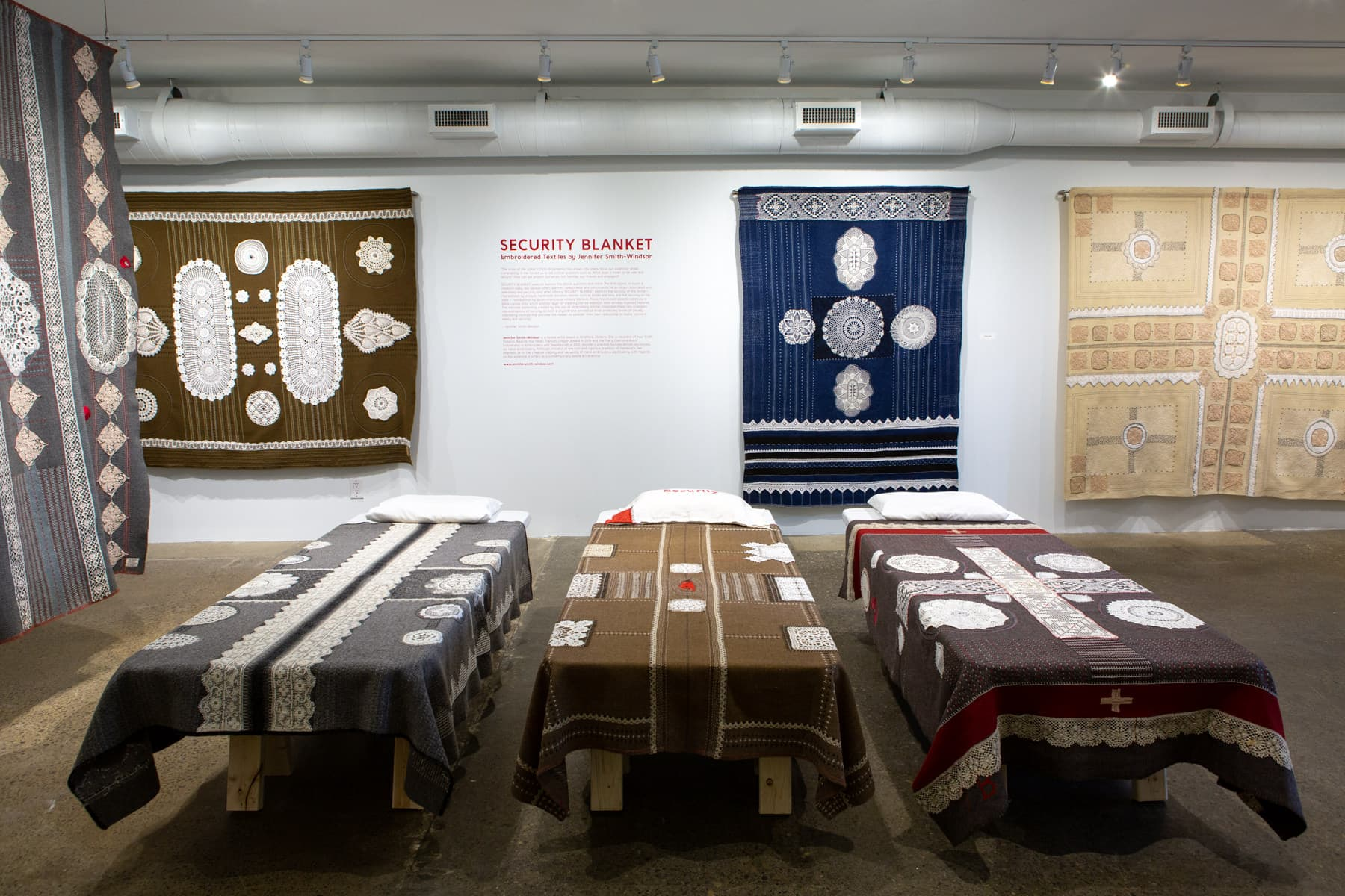 Image description: Embroidered wool blankets made up like beds and hung from gallery walls.